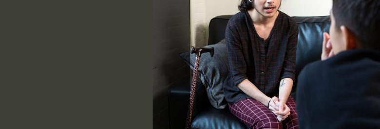 A genderqueer person sits on a leather couch with their hands clasped. Their cane rests against the couch beside them. Their face is cropped out just above their nose. They are speaking with someone in the foreground facing away from the viewer and leaning forward to listen.