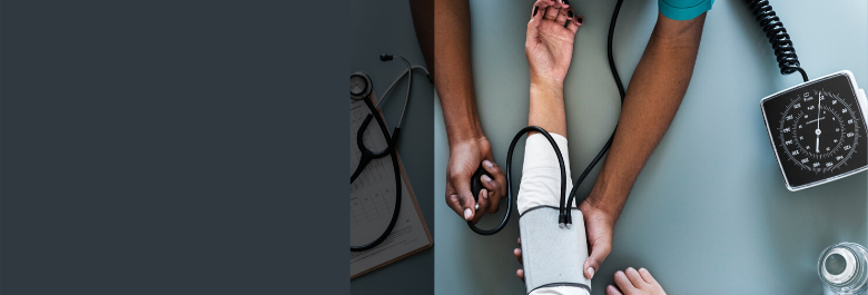 From overhead a Black health provider takes the blood pressure of another tanned skinned individual. A clipboard and stethoscope is also pictured to portray a health setting.