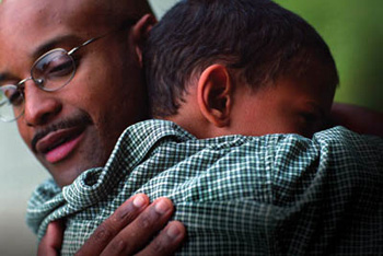 An African American man hugs his son