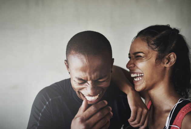 A young Black couple laughs together. The man is looking down with a hand up to his mouth, the woman is leaning on his shoulder and laughing.